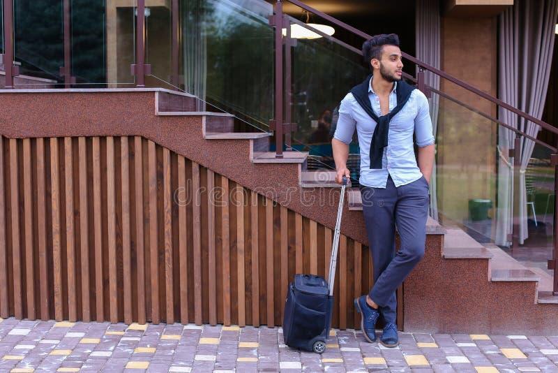 Aantrekkelijke jonge Arabische mens die zich met in hand koffer en p bevinden royalty-vrije stock fotografie