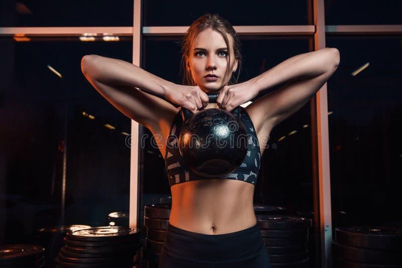 Aantrekkelijke jonge atleet met het spierlichaam uitoefenen crossfit Vrouw in sportkleding die crossfit training met ketel doen royalty-vrije stock fotografie