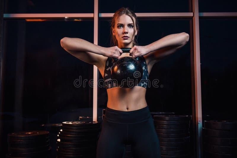 Aantrekkelijke jonge atleet met het spierlichaam uitoefenen crossfit Vrouw in sportkleding die crossfit training met ketel doen royalty-vrije stock afbeeldingen