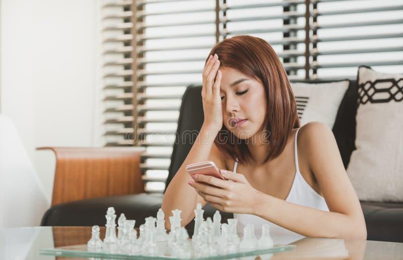 Aantrekkelijke Jonge Aziatische vrouw die een het slimme telefoon en texting gebruiken royalty-vrije stock afbeelding