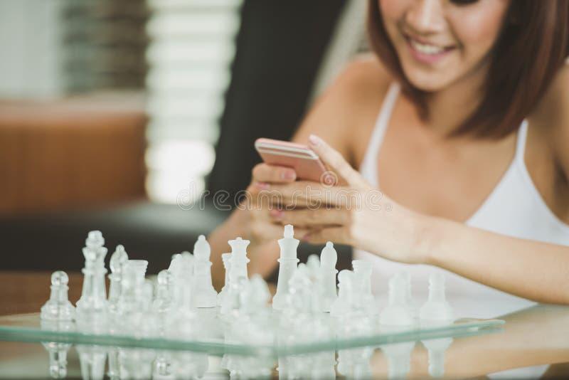 Aantrekkelijke Jonge Aziatische vrouw die een slimme telefoon met behulp van royalty-vrije stock afbeelding