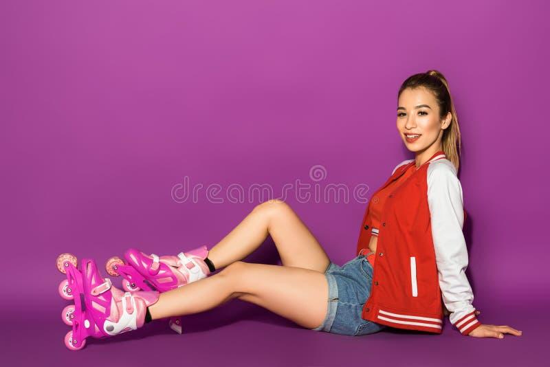 aantrekkelijke jonge Aziatische vrouw in rolschaatsen die en bij camera zitten glimlachen stock afbeeldingen