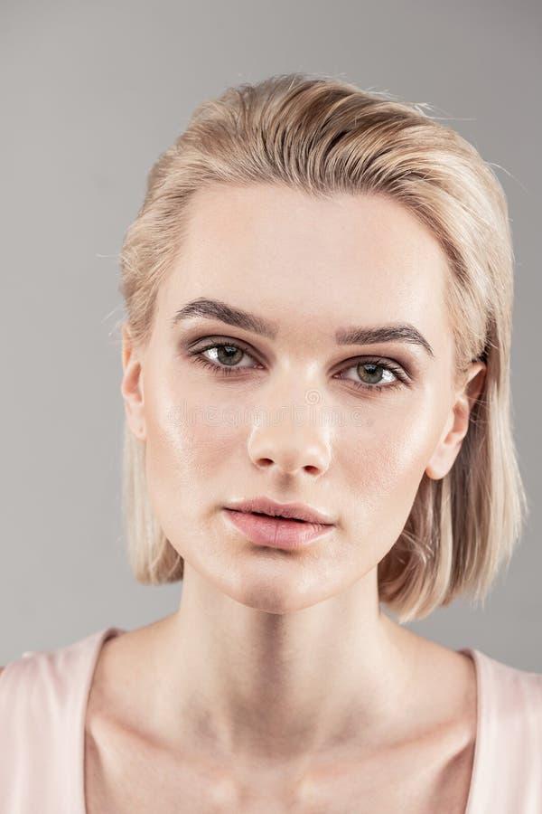 Aantrekkelijke jonge dame met het korte blondehaar stellen voor cameraman stock afbeeldingen