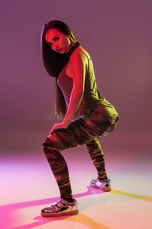 Aantrekkelijke jonge donkerbruine vrouw in de studio het dansen Buitdans op een donkere achtergrond royalty-vrije stock afbeelding
