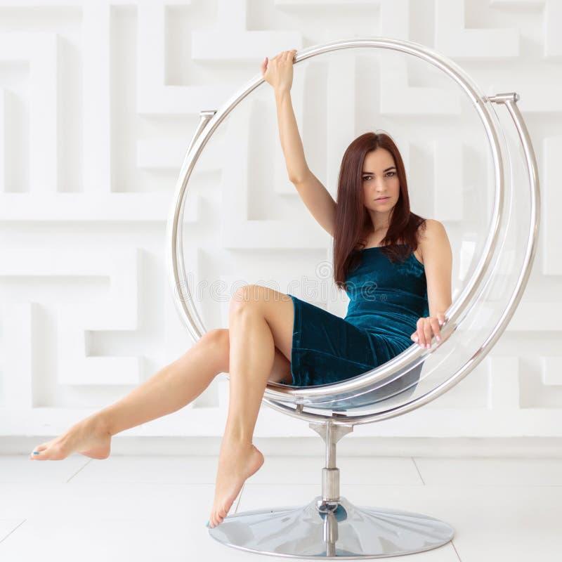 Aantrekkelijke jonge donkerbruine vrouw die elegante kledingszitting als ronde glasvoorzitter dragen royalty-vrije stock afbeeldingen