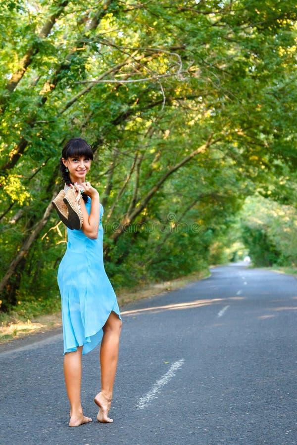 Aantrekkelijke jonge donkerbruine vrouw die op lege weg bij som lopen stock afbeelding