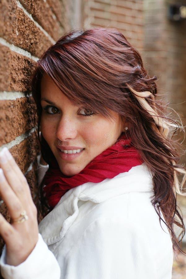 Aantrekkelijke jonge donkerbruine vrouw die in openlucht stellen royalty-vrije stock afbeelding