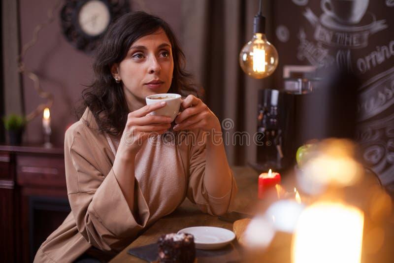 Aantrekkelijke jonge Kaukasische vrouw het drinken koffie in een koffiewinkel bij de barteller royalty-vrije stock foto's