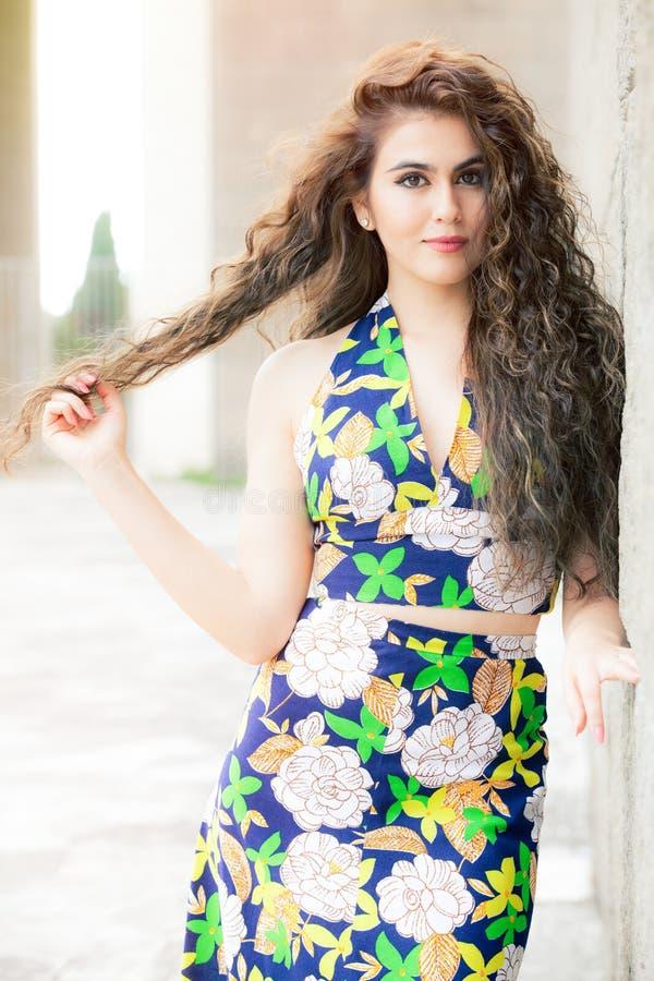 Aantrekkelijke jonge mannequin krullende vrouw in openlucht, bloemrijke kleding stock afbeeldingen