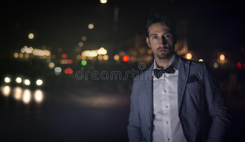 Aantrekkelijke jonge mens bij nacht met stadslichten achter hem royalty-vrije stock afbeeldingen