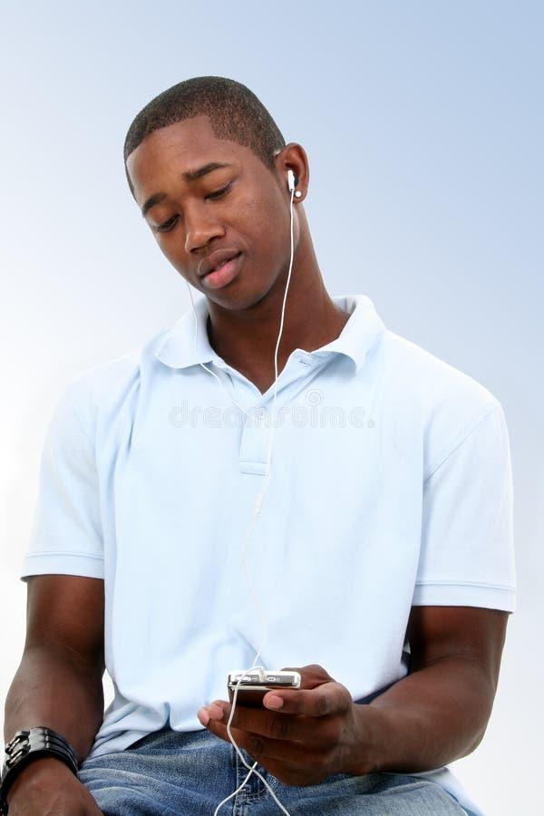 Aantrekkelijke Jonge Mens die aan Hoofdtelefoons luistert stock afbeelding