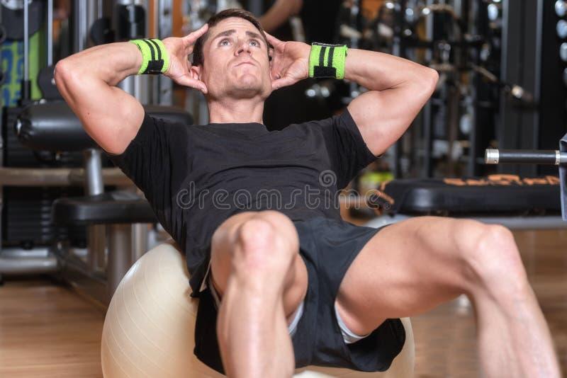 Aantrekkelijke jonge mens die oefeningsbal in een gymnastiek gebruiken Aantrekkelijke jonge mens die abs uitoefenen stock afbeeldingen