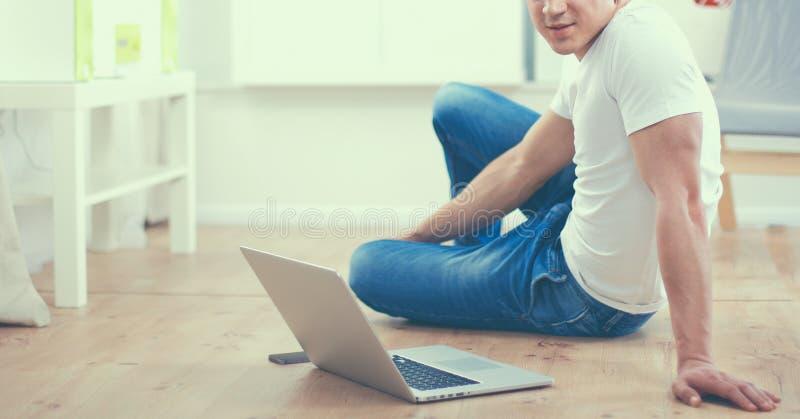 Aantrekkelijke jonge mens die op houten vloer liggen en laptop met behulp van stock afbeeldingen