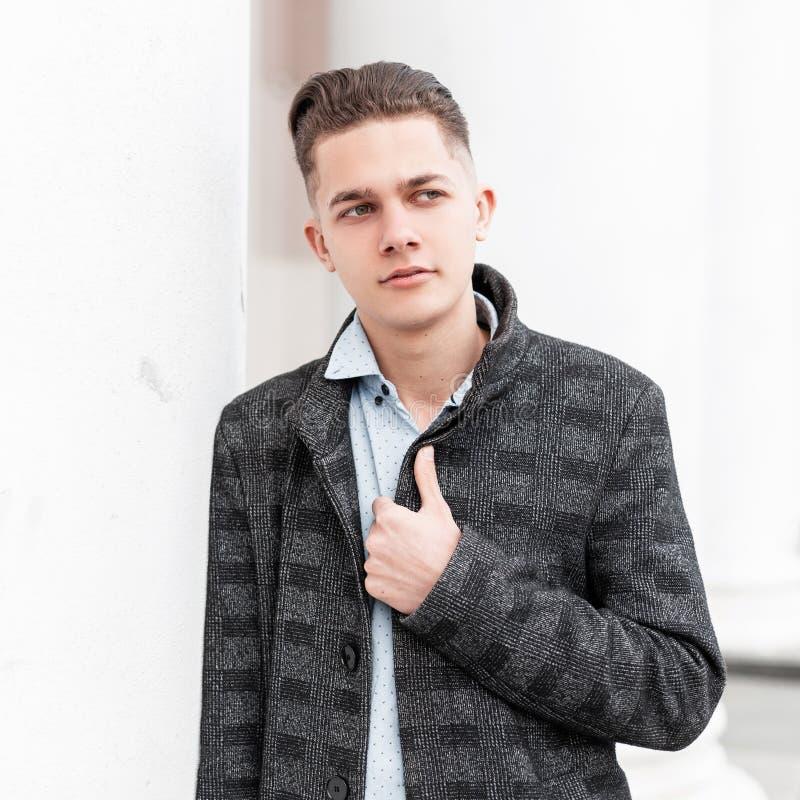 Aantrekkelijke jonge mens in een klassiek plaidjasje in een modieus overhemd met het modieuze kapsel stellen in een stad stock fotografie