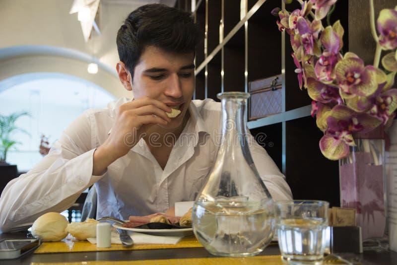 Aantrekkelijke jonge mens in het elegante restaurant eten royalty-vrije stock foto's
