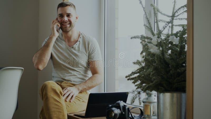 Aantrekkelijke jonge mens het spreken telefoonzitting op vensterbank met laptop en camera thuis stock foto's