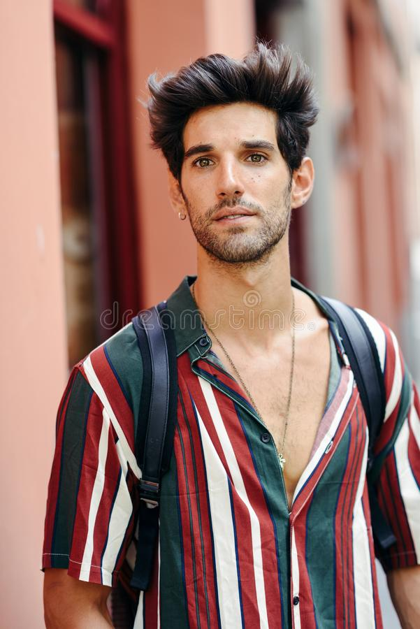 Aantrekkelijke jonge mens met donker haar en modern kapsel die vrijetijdskleding in openlucht dragen stock foto