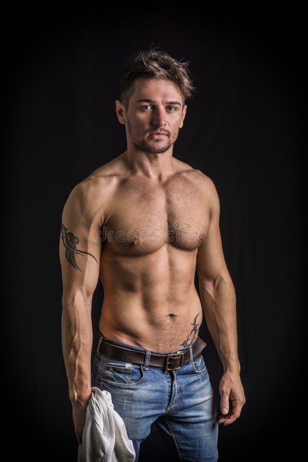 Aantrekkelijke jonge mens met naakt spiertorso, die jeans dragen stock afbeeldingen