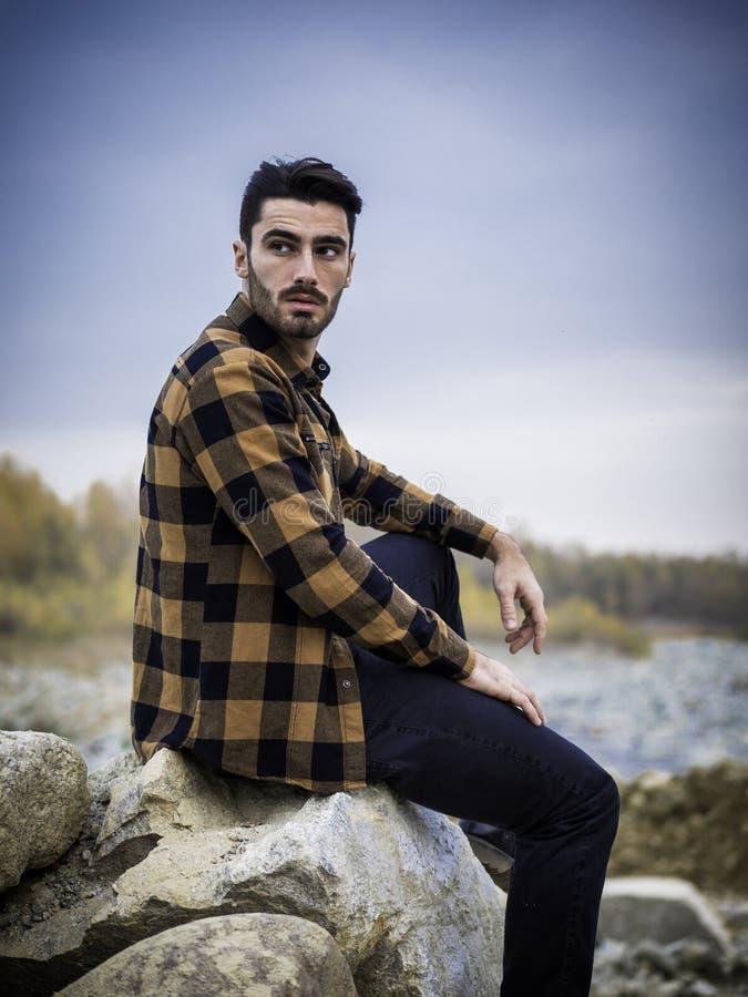 Aantrekkelijke jonge mens op een meer in zonnig stock afbeeldingen