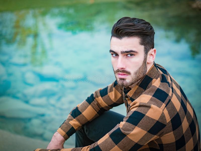 Aantrekkelijke jonge mens op een meer in zonnig stock foto's
