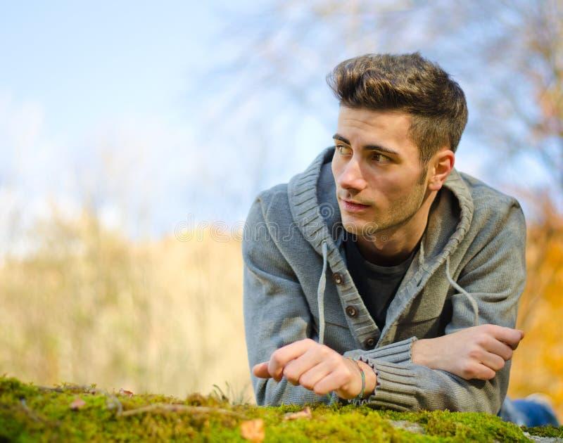 Aantrekkelijke jonge mens in openlucht in aard die op mos liggen royalty-vrije stock afbeeldingen