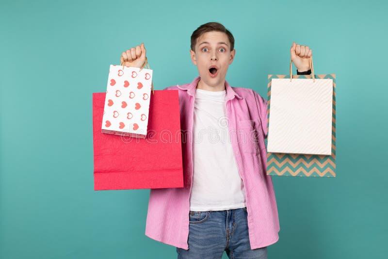 Aantrekkelijke jonge mens in roze overhemd met kleurrijke het winkelen zakken in handen, die over blauwe achtergrond wordt ge?sol stock fotografie