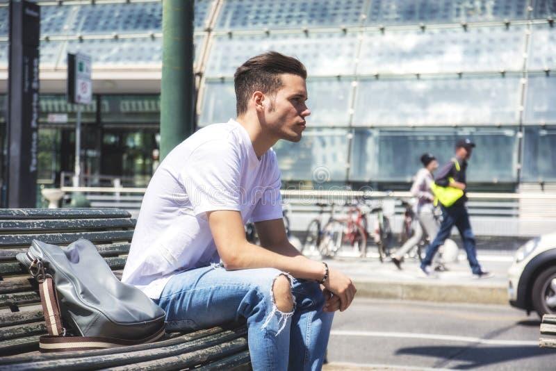 Aantrekkelijke jonge mens in stad, het zitten royalty-vrije stock afbeelding
