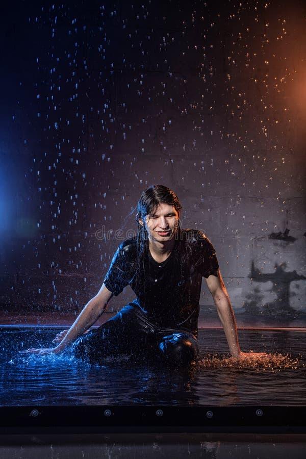 Aantrekkelijke jonge mens in zwarte natte kleren onder de regen en de plons van water, studiofoto royalty-vrije stock fotografie