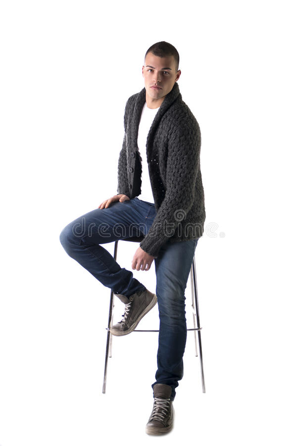 Aantrekkelijke jonge mensenzitting op kruk met wolsweater en jeans stock afbeelding