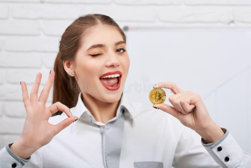 Aantrekkelijke jonge modelholdings gouden bitcoin en het tonen van o.k. teken stock foto's
