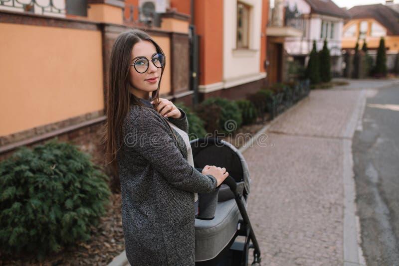 Aantrekkelijke jonge moeder die met haar weinig baby lopen Mamma met pasgeboren baby in kinderwagen stock fotografie