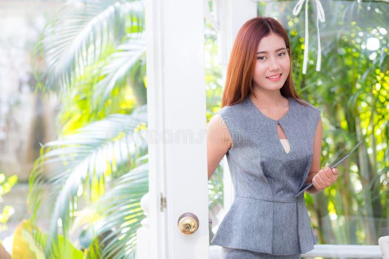 Aantrekkelijke jonge onderneemster die de buitendeur openen voor een tuin royalty-vrije stock afbeelding