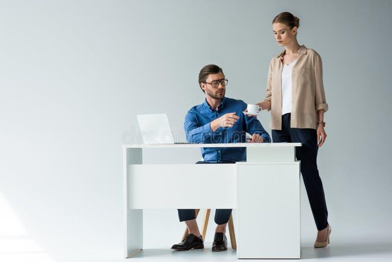 aantrekkelijke jonge secretaresse die kop van koffie overgaan tot werkgever stock afbeeldingen