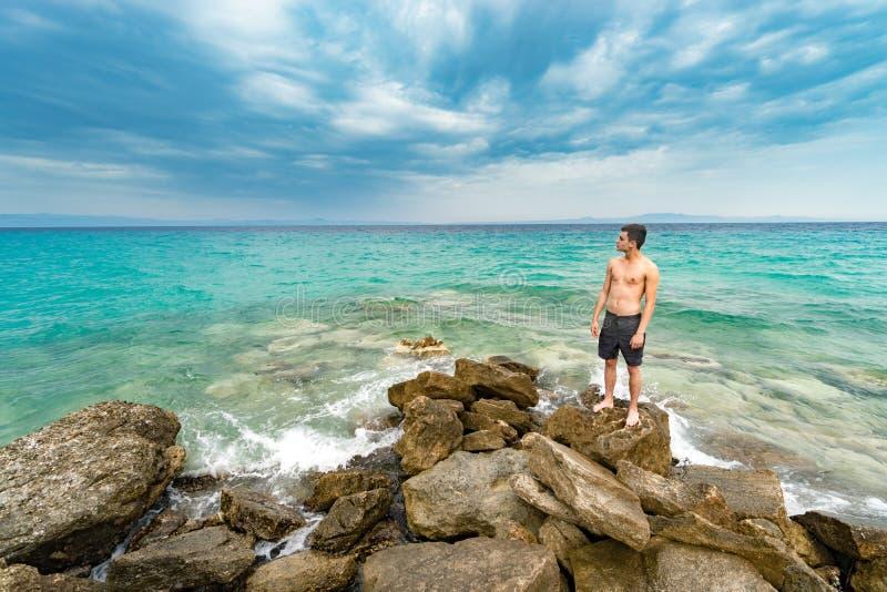 Aantrekkelijke jonge shirtless atletische die mens op geïsoleerd eiland wordt verloren die zich op rots bevinden stock afbeeldingen