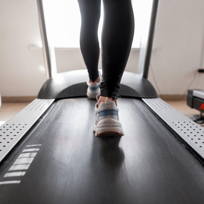 Aantrekkelijke jonge sportieve vrouw die in de gymnastiek uitwerkt Het meisje doet cardio opleiding op tredmolen Het lopen op een stock fotografie