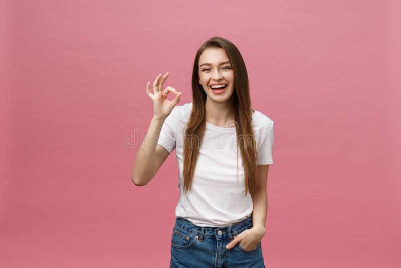 Aantrekkelijke jonge volwassen vrouw die o.k. teken tonen Van het uitdrukkingsemotie en gevoel concept Studioschot, op roze wordt stock afbeeldingen