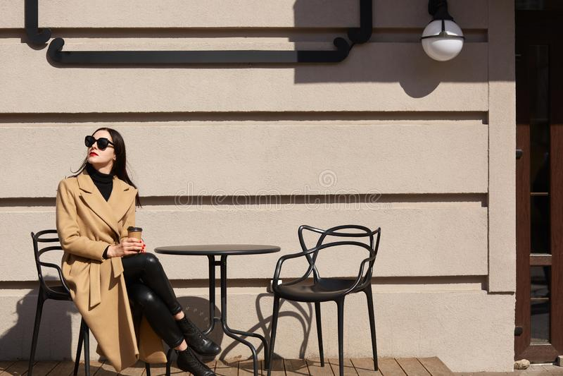 Aantrekkelijke jonge vrouw in bruine laag en zwarte zonnebril, sittig openluchtrestaurant Lief donkerbruin meisje die coffe binne royalty-vrije stock foto's