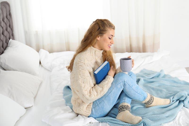 Aantrekkelijke jonge vrouw in comfortabele warme sweater met kop van hete drank en boekzitting op bed stock foto