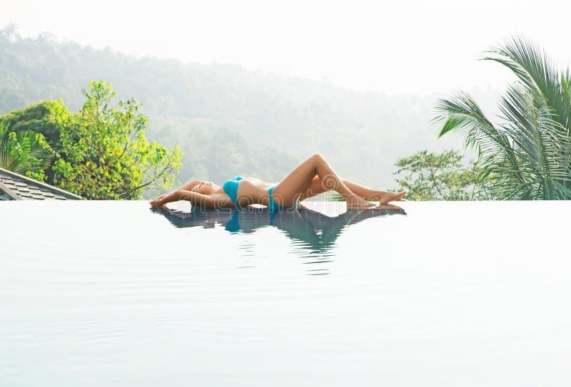 Aantrekkelijke, jonge vrouw in cyaanzwempak het liggen poolside royalty-vrije stock fotografie