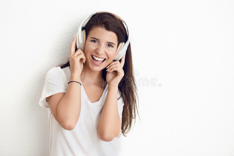 Aantrekkelijke jonge vrouw die aangezien zij aan muziek op stereohoofdtelefoons luistert lachen stock foto
