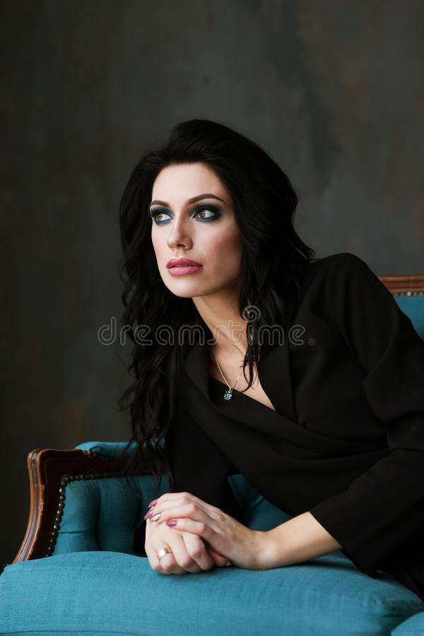 Aantrekkelijke jonge vrouw die bij de bank liggen Hoogste mening mooi brunette in een zwart jasje royalty-vrije stock afbeeldingen