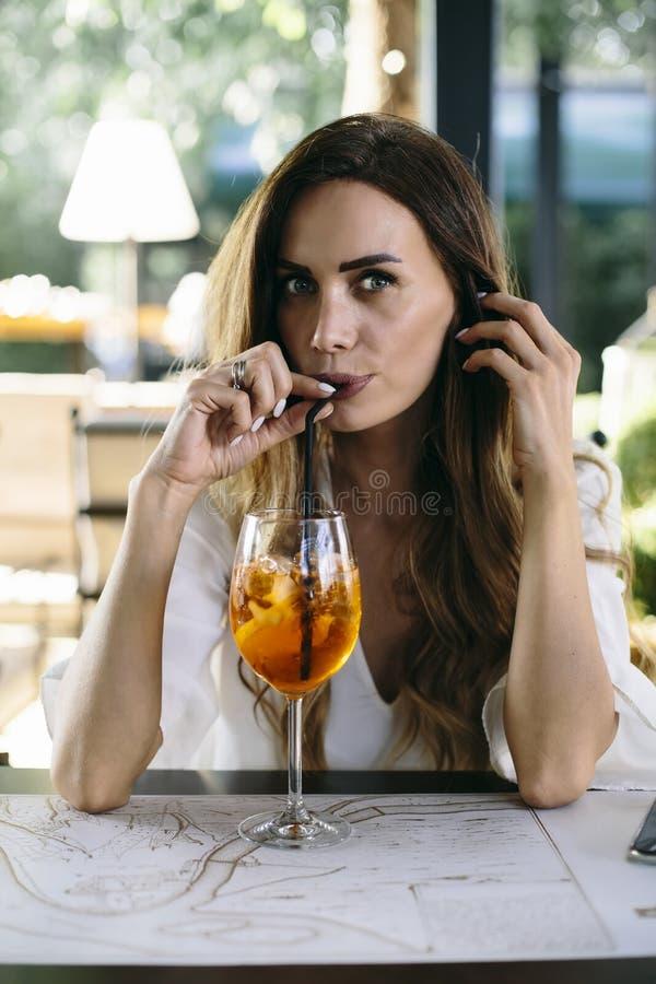 Aantrekkelijke jonge vrouw die coctail in koffie drinken openlucht royalty-vrije stock afbeelding