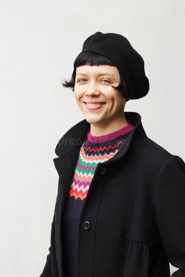 Aantrekkelijke jonge vrouw die een baret dragen stock fotografie
