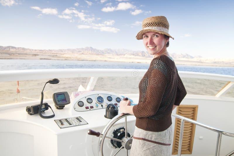 Aantrekkelijke jonge vrouw die een boot stuurt stock foto
