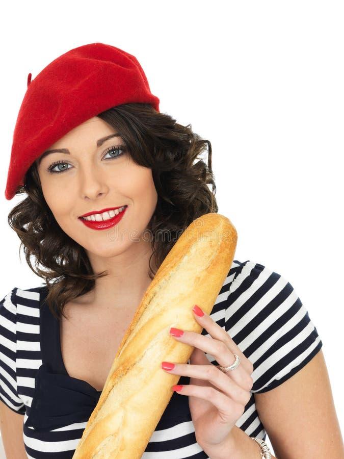 Aantrekkelijke Jonge Vrouw die een Frans Brood van het Stokbrood eten royalty-vrije stock foto's
