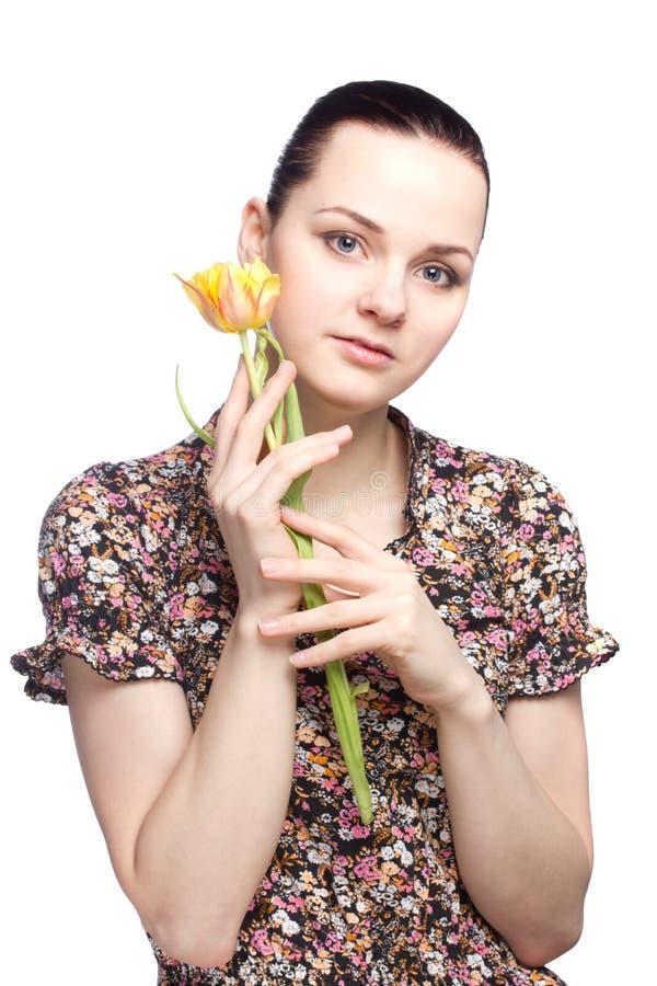 Aantrekkelijke jonge vrouw die een gele tulp houden royalty-vrije stock afbeeldingen
