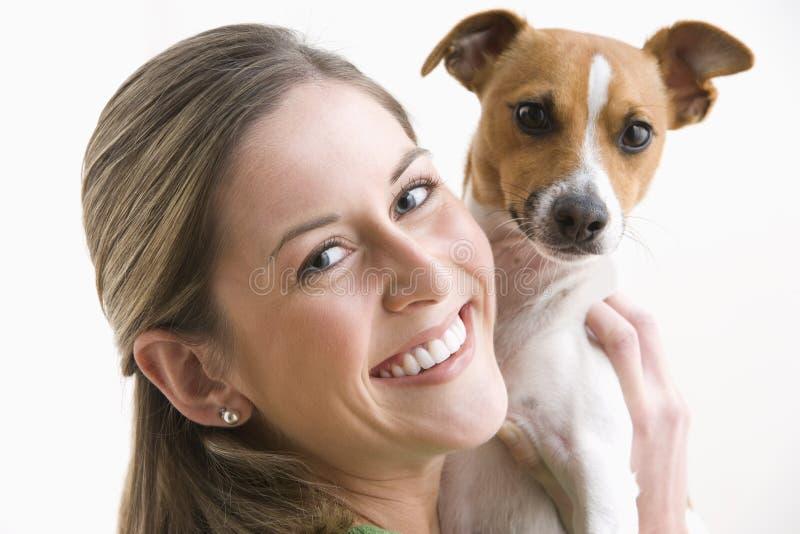 Aantrekkelijke Jonge Vrouw die een Hond en het Glimlachen houdt royalty-vrije stock afbeelding
