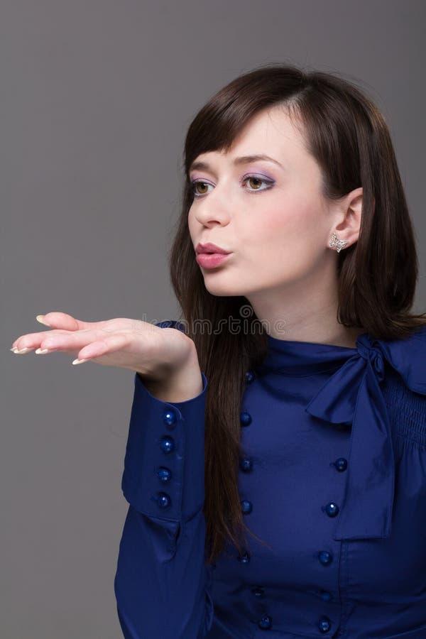 Aantrekkelijke jonge vrouw die een kus blaast royalty-vrije stock fotografie
