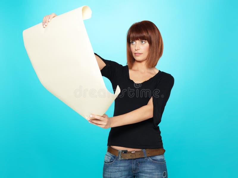 Aantrekkelijke jonge vrouw die een tekening bekijkt stock afbeeldingen