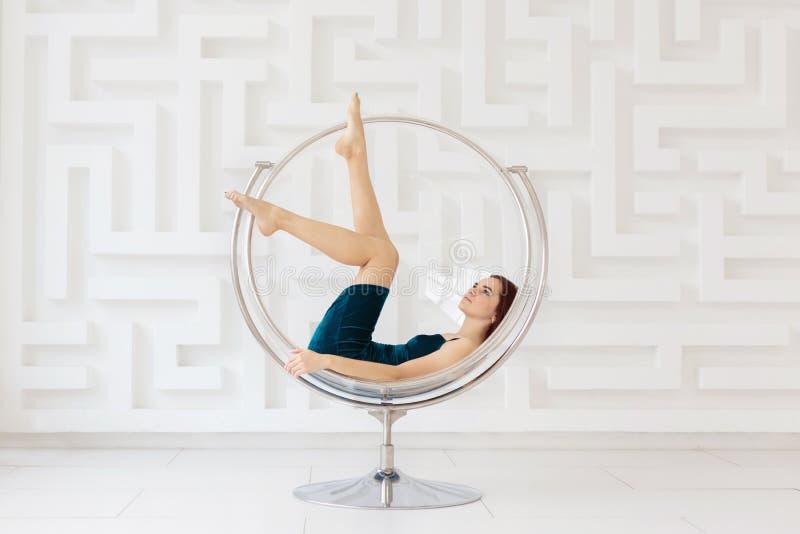 Aantrekkelijke jonge vrouw die elegante blauwe kleding dragen die op ronde glasstoel in witte ruimte liggen royalty-vrije stock afbeeldingen